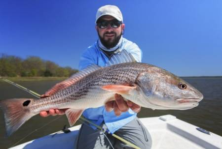 A fishermen holds a redfish