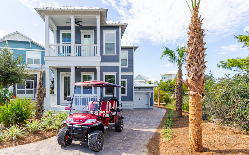 A golf cart is parked outside of a 30A vacation rental